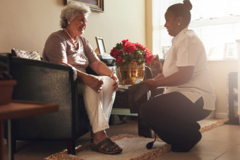 Senior women sitting on a chair at home with female caregiver holding blood pressure gauge.
